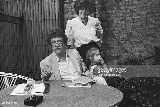 Kurt Vonnegut relaxes at a table with his wife Jill Krementz and daughter Lily at his side