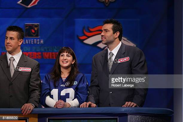Kurt Warner of the New York Giants looks on with his favorite Giants fan during the Wheel of Fortune NFL Players Week taping on December 7 2004 at...