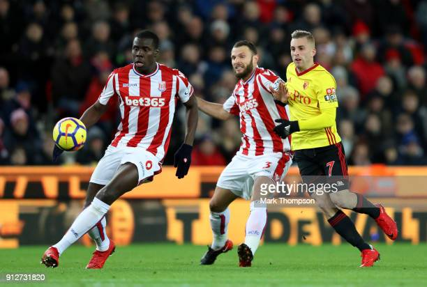 Kurt Zouma of Stoke City controls the ball under pressure from from Gerard Deulofeu of Watford who is held off by Erik Pieters of Stoke City during...