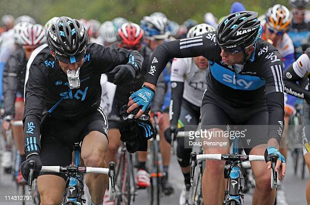 KurtAsle Arvesen of Norway and teammate Ian Stannard of Great Britain riding for Sky Procycling eat and change clothes after passing through the feed...