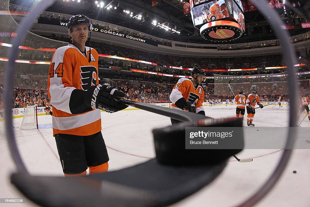 Kurtis Foster #3 of the Philadelphia Flyers passes a puck through a hole to a fan during warmups prior to the game against the New York Rangers at the Wells Fargo Center on March 26, 2013 in Philadelphia, Pennsylvania.