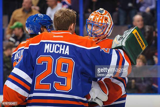 Kurtis Mucha of the Edmonton Oilers congratulates teammate Ben Scrivens after a victory over the Ottawa Senators during an NHL game at Rexall Place...