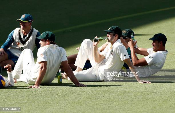 Kurtis Patterson and Mitchell Starc of Australia and team mates celebrate on the ground after day four of the Second Test match between Australia and...