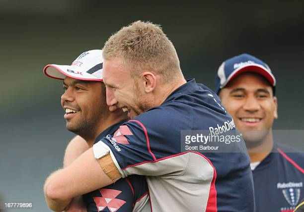 Kurtley Beale is hugged by teammate James King as Cooper Vuna looks on during a Melbourne Rebels Super Rugby training session at AAMI Park on April...