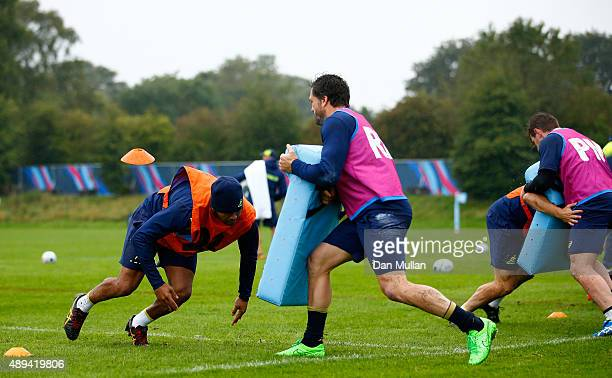 Kurtley Beale of Australia prepares to hit a tackle pad held by Adam AshleyCooper of Australia during a training session at the University of Bath on...
