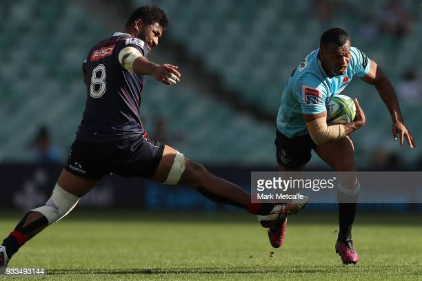 Kurtley Beale of the Waratahs evades the outstretched leg of Amanaki Mafi of the Rebels during the round five Super Rugby match between the Waratahs...