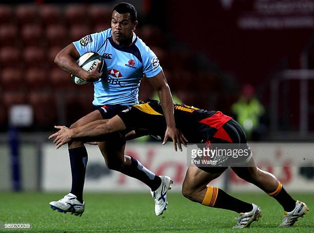 Kurtley Beale of the Waratahs is tackled by Jackson Willison of the Chiefs during the round 13 Super 14 match between the Chiefs and the Waratahs at...