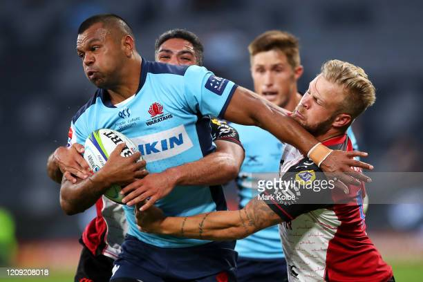 Kurtley Beale of the Waratahs is tackled by Tyrone Green of the Lions during the round five Super Rugby match between the Waratahs and the Lions at...