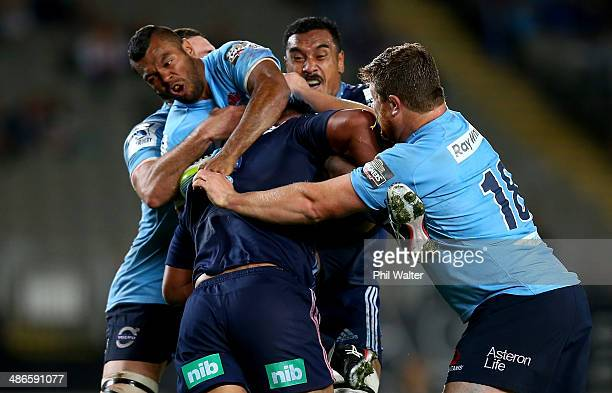 Kurtley Beale of the Waratahs is tackled during the round 11 Super Rugby match between the Blues and the Waratahs at Eden Park on April 25 2014 in...