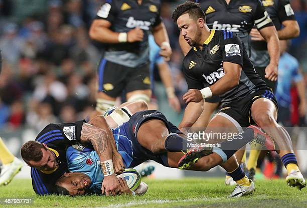 Kurtley Beale of the Waratahs is tackled just short of the try line during the round 12 Super Rugby match between the Waratahs and the Hurricanes at...