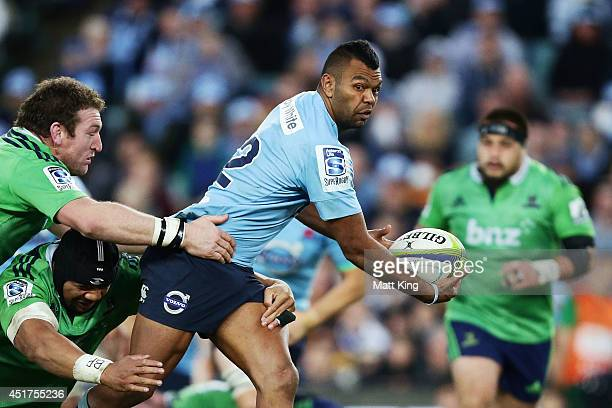 Kurtley Beale of the Waratahs offloads the ball in a tackle during the round 18 Super Rugby match between the Waratahs and the Highlanders at Allianz...