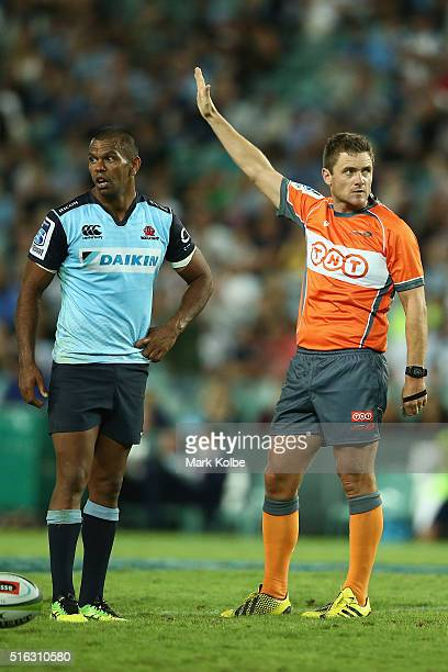Kurtley Beale of the Waratahs watches on as referee Nick Briant awards a penalty during the Super Rugby match between the New South Wales Waratahs...