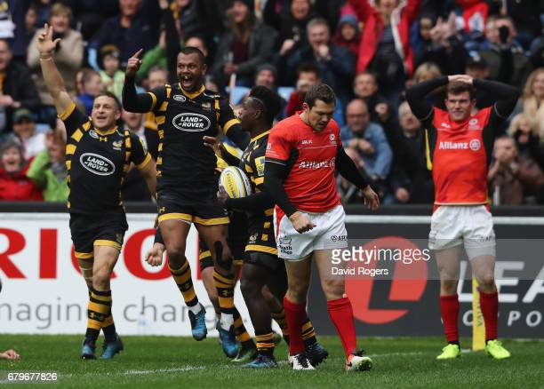 Kurtley Beale of Wasps celebrates as team mate Christian Wade touches down for a try during the Aviva Premiership match between Wasps and Saracens at...