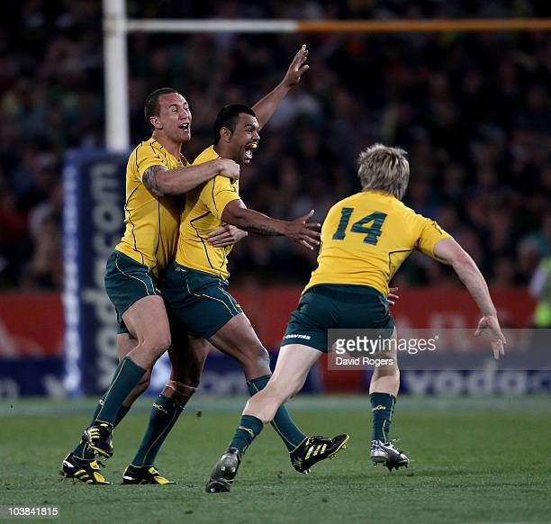 Kurtley Beale the Wallaby fullback celebrates with team mates Quade Cooper and James O'Connor after scoring the match winning penalty during the 2010...
