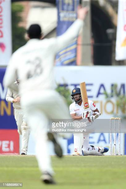 Kusal Mendis of Sri Lanka reacts after his dismissal while William Somerville of New Zealand celebrates during day five of the First Test match2...