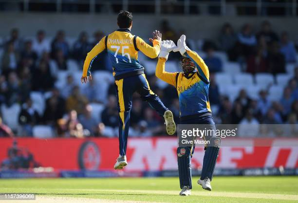 Kusal Perera of Sri Lanka celebrates the wicket of Chris Woakes of England with bowler Dhananjaya de Silva of Sri Lanka during the Group Stage match...