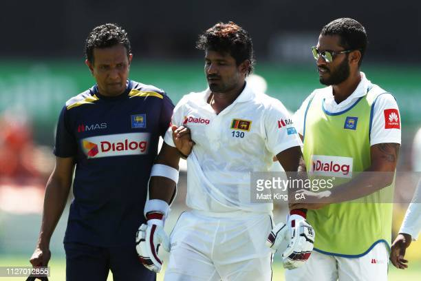 Kusal Perera of Sri Lanka is assisted by medival staff and retires hurt after being hit by a ball from Jhye Richardson of Australia during day three...