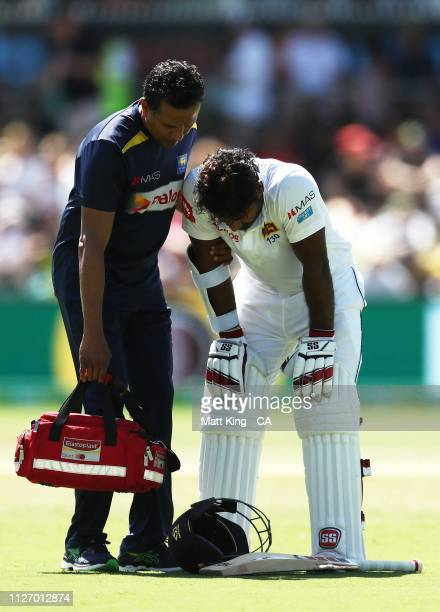 Kusal Perera of Sri Lanka is assisted by medival staff before retiring hurt after being hit by a ball from Jhye Richardson of Australia during day...