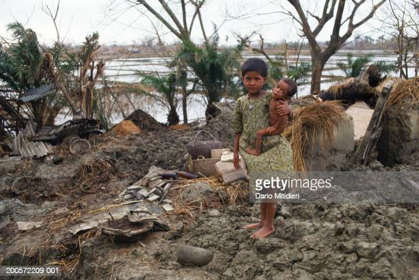 Kutubdia Island Bangladesh Child carries infant amongst wreckage after a cyclone hit Kutubdia Island 40000 of population of 110000 reported dead...