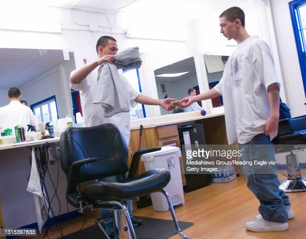 Kutztown, PA 200700182- Dylan Murphy of Whitehall pays barber Jon Escueta after getting his hair cut .The City Cuts Barbershop on North Constitution...