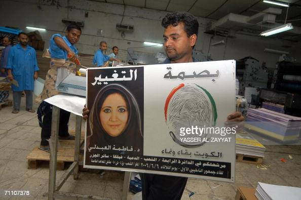 A worker at printing press carries campaign posters for Kuwaiti