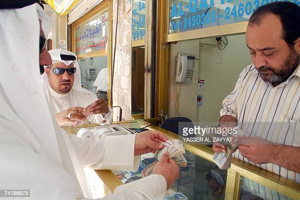 Kuwaiti citizens buy US dollars from a currency exchange in Kuwait City 20 May 2007 Kuwait today pegged its dinar to a basket of international...