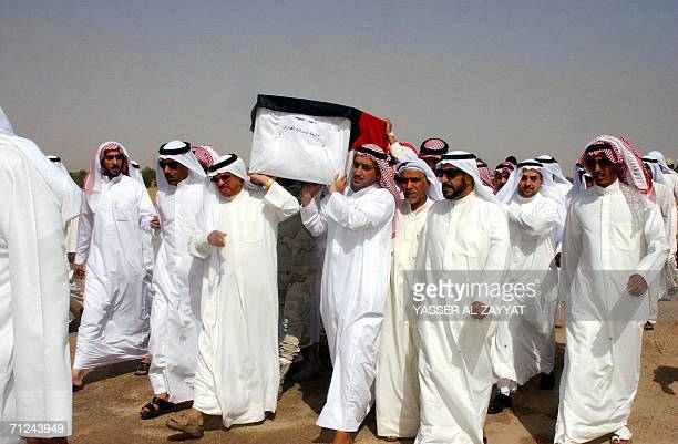 Kuwaiti mourners carry the coffin of one of three Kuwaitis found recently in a mass grave in Iraq during a funeral 20 June 2006 at a cemetary in...