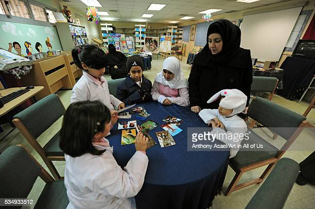 Kuwait Kuwait City children looking at photographs from other children around the world during Art in All of Us activities