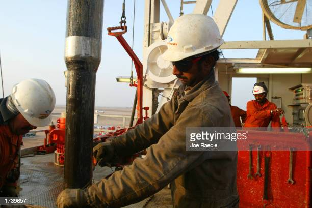 Kuwait Oil Company workers change pipes on a drilling rig January 22 2003 on the northern border between Iraq and Kuwait in Kuwait Kuwait produces...