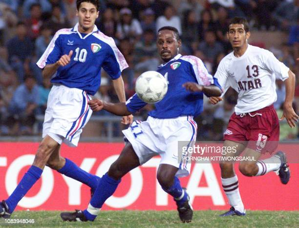Kuwait 's football player Faraj Laheeb and AlSager Hani fight for the ball with Qatar's Al Shammar Saghayer during play in the quarter final round in...
