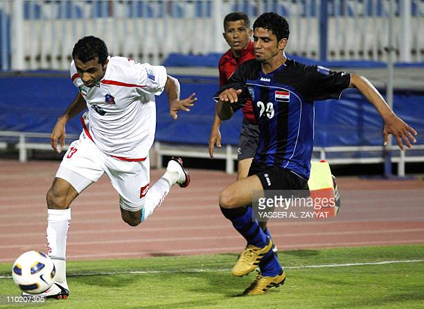 Kuwait SC club player Ismail Ashur runs with the ball past Abbas Qassem of Iraq's AlTalaba club during their 2011 AFC Cup football match in Kuwait...