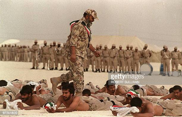 A Kuwaiti army drill instructor walks across the backs of volunteers during graduation exercices of few members of the Kuwaiti army 05 January in a...