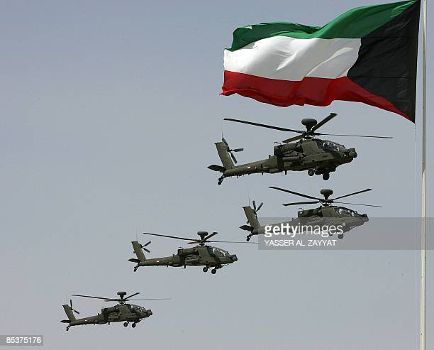 Kuwaiti army helicopters fly past a national flag during a military parade in Kuwait City on March 11 2009 The show was held to mark the Emir of...