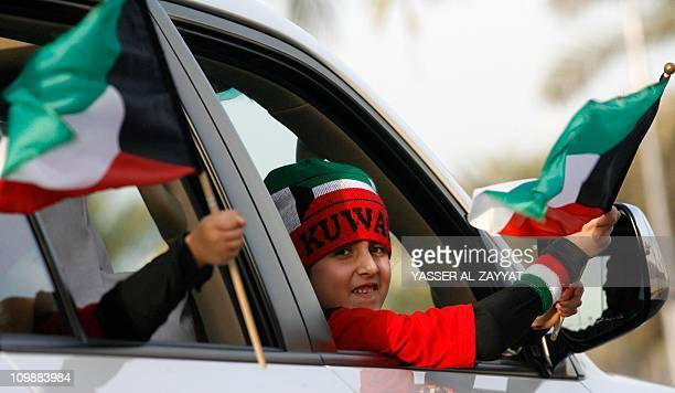 A Kuwaiti boy waves a bational flag as he drives with his family through Kuwait City during national celebrations on February 24 2011 on the eve of...