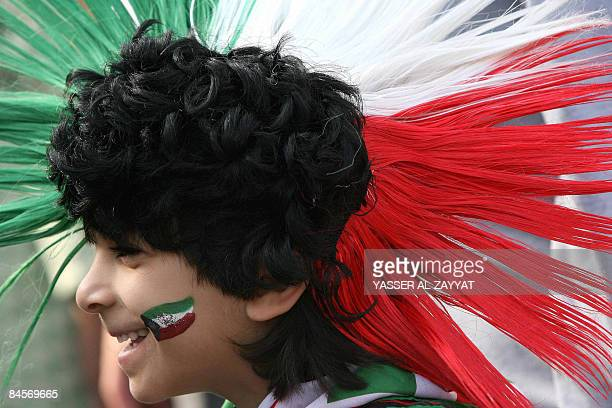 A Kuwaiti child parades with the colours of the national flag during celebrations marking the launching of the Hala shopping festival on January 31...