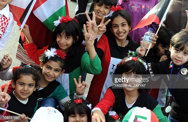 Kuwaiti children dressed in the colours of their national flag flash the victory sign in Kuwait City on February 17 2011 as festivals take place to...