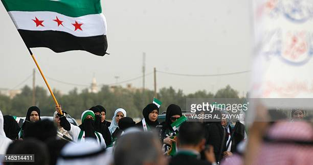 Kuwaiti citizens and Syrians residents hold up the adopted Syrian revolutionary flag during a protest in front of the Syrian Embassy in Kuwait City...