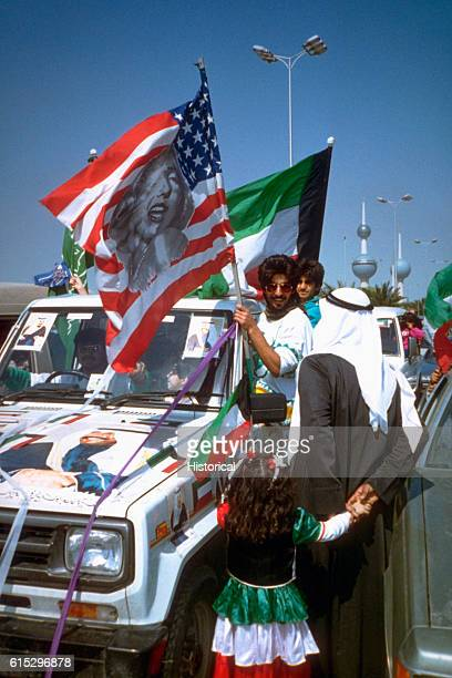 Kuwaiti citizens in automobiles and on foot celebrate the retreat of Iraqi forces from Kuwait as a result of Operation Desert Storm Kuwait City 1991