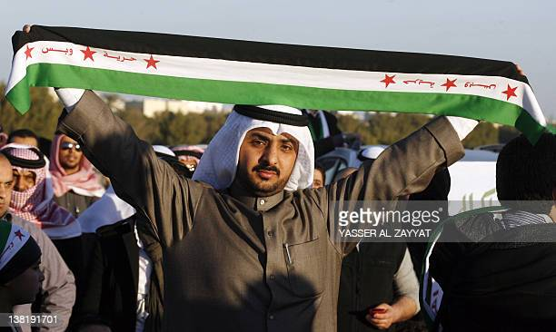 A Kuwaiti demonstrator holds the preBaath Syrian flag reading Freedom Only outside the Syrian embassy in Kuwait City during a protest against the...