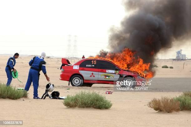 Kuwaiti driver Salem alThafiri and his Kuwaiti codriver Faris look at their burning Mitsubishi Lancer Evolution VIII during the Kuwait International...