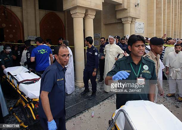 Kuwaiti emergency personnel pull stretchers past security forces outside the Shiite AlImam alSadeq mosque after it was targeted by a suicide bombing...