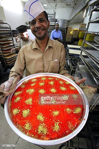 A Kuwaiti employee displays a tray of traditional arab sweets at a sweets shop during the Muslim fasting month of Ramadan on June 20 in Kuwait City...