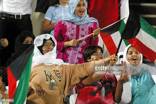 Kuwaiti fans hold up their national flags during during a group B qualifying match of the Asian football championship between Kuwait and Palestine...