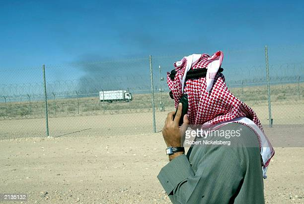 A Kuwaiti government employee standing in the Ratqa oil field speaks on his cell phone February 6 2003 while looking at an Iraqi oil well burning...