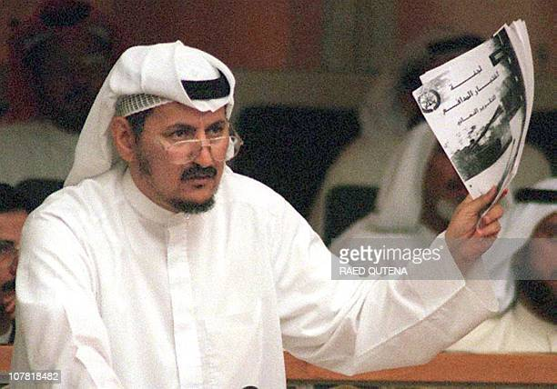 Kuwaiti Islamic opposition member of the Parliament Mubarak alDuwailah gestures with a report from the ministry of defense during a parliament...