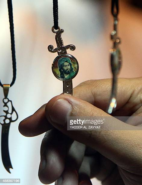 A Kuwaiti looks at a pendant bearing an image of Imam Hussein one of Shiite Islam's most revered figures during Ashura commemorations that mark Imam...