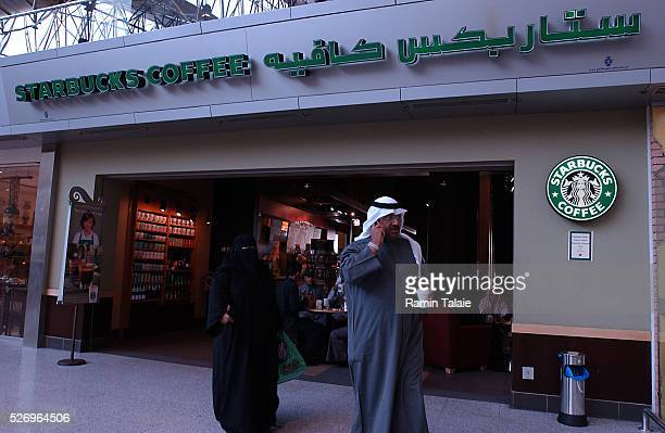 A Kuwaiti man holding a cup of coffee and his wife walk out of a Starbucks Coffee outlet in a Kuwait City shopping center on February 28 2005 Despite...