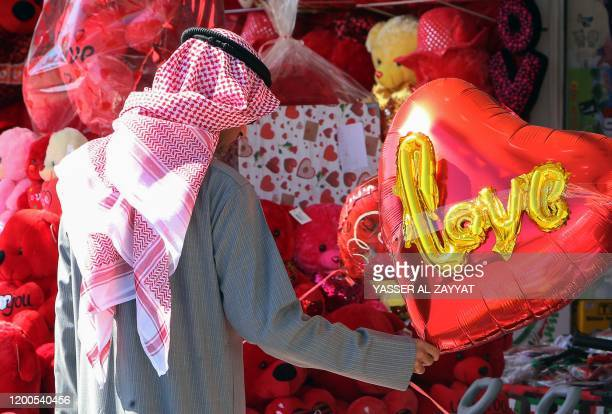 A Kuwaiti man holds a heartshaped balloon on display outside a shop in Kuwait City on February 13 2020 ahead of Valentine's day
