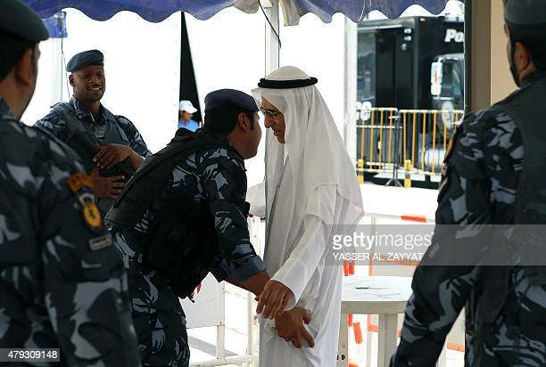 A Kuwaiti man is searched by security members outside the Sunni Grand Mosque as Sunni and Shiite worshipers arrive to perform Friday prayers together...