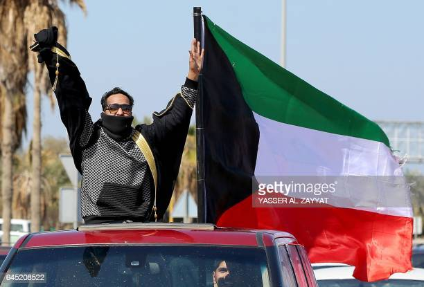 A Kuwaiti man rides a car mounted with a national flag during celebrations marking the country's 56th Independence Day and the 26th anniversary of...